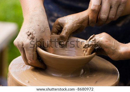 A potters hands guiding a child hands to help him to work with the ceramic wheel See similar photos in my portfolio.