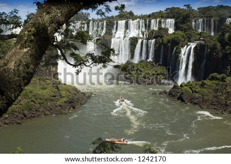 A power boat approaches a waterfall.