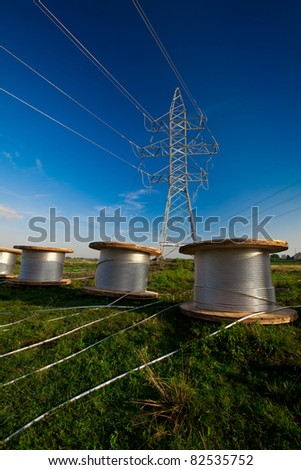 A power line tower in the field and bobbins with aluminum wire ready to installation