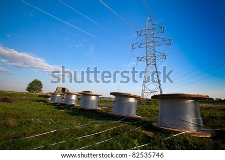 A power line tower in the field and five bobbins with aluminium wire ready to installation