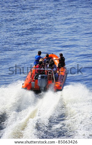 A powerboat heading out to sea at high speed leaving a white wake. Space for text on the water at top