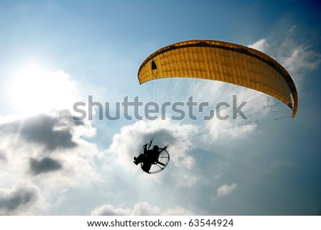 A powered paraglider pilot in flight with a blue cloudy sky in the background