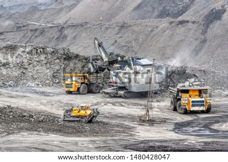 A powerful excavator loads mining trucks. Excavation and loading of rock mass into transport. #1480428047