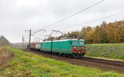 A powerful green two-piece DC electric locomotive pulls a long, heavy freight train along a curved railway line. Autumn shot.