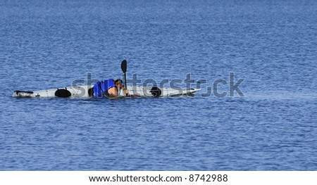 A powerful male kayaker performs float-asisted roll in calm waters of Mission Bay, San Diego, California. Copyspace on top and bottom. - stock photo