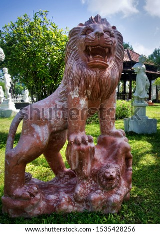 A powerful red marble lion. Stone and rock carvings from central Vietnam. Sculpture and skilled artisan work.