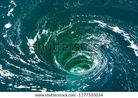 Photo of  A powerful whirlpool is generated at the surface of the green waters of the river Rance by the action of a turbine of the tidal power station near Saint-Malo in Brittany, France.