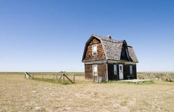 A prairie homestead house on a skyless day.