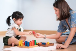 A precious moment of adorable little girl 2 years old, learn by play wooden colorful blocks with her beautiful mother. Early education, Preschool, Montessori at home, Child development concept, Asian.
