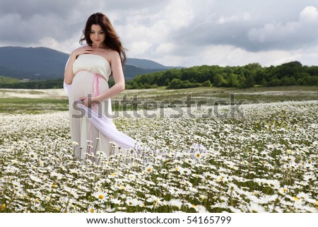 A pregnant girl in a field of flowers