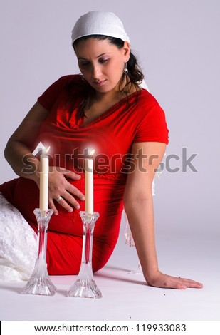 A pregnant Jewish woman is lighting the sabbath candles