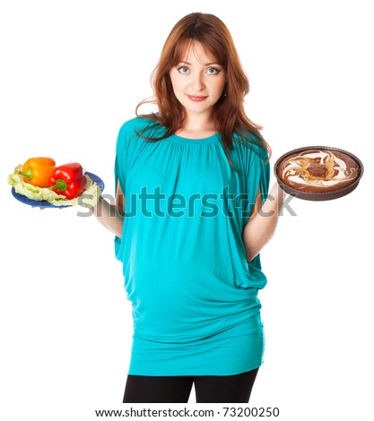 A pregnant smiling young woman is holding food in her hands. Isolated on a white background