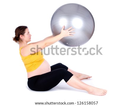 A pregnant woman doing a breathing exercise with an exercise ball