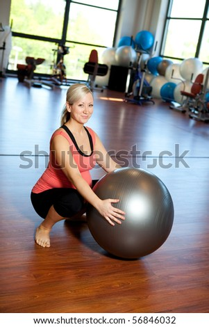 A pregnant woman doing a side squatting exercise for the leg muscles using afitball in an exercise studio.