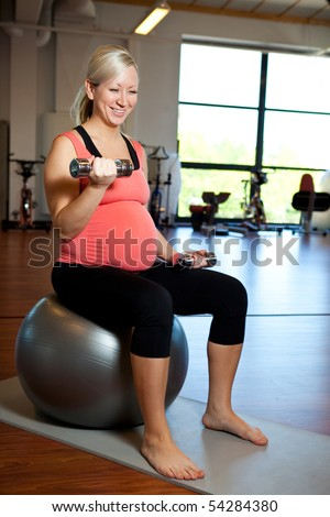 A pregnant woman doing bicep muscle exercises using dumbbells while seated on a fitness ball