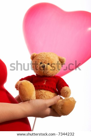 a pregnant woman holding a bear and balloon