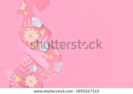 A pregnant woman hugs her stomach on a pink background. The concept of the birth of a child. Duration of pregnancy. Waiting for the birth of a child. Mother's love. Cut out the paper. Spring flowers.
