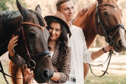 a pregnant woman in a hat and her husband in white clothes stand next to horses in the forest in nature.Stylish pregnant woman with a man with horses.Family.