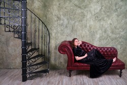A pregnant woman in an evening dress is lying on a red sofa by the old spiral staircase. Retro full-length portrait of a pregnant woman