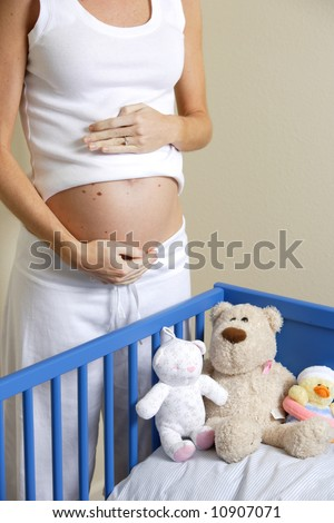 A pregnant woman loves her un-born baby near a crib with stuffed animals