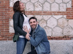 A pregnant woman standing in front of a brick building. Man hugs her belly. Couple.