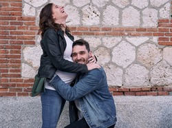 A pregnant woman standing in front of a brick building. Man hugs her belly. Happy couple.