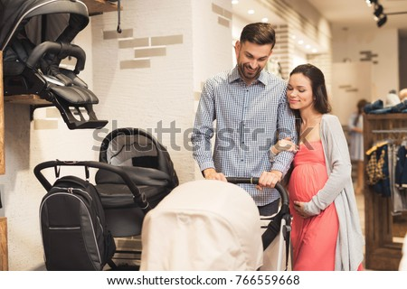 A pregnant woman together with a man choose a baby carriage. They together came for shopping in the shopping center. They are preparing to become parents and choose things for their future child.