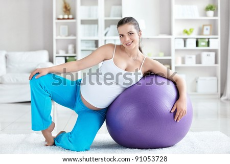 A pregnant woman with a ball at home