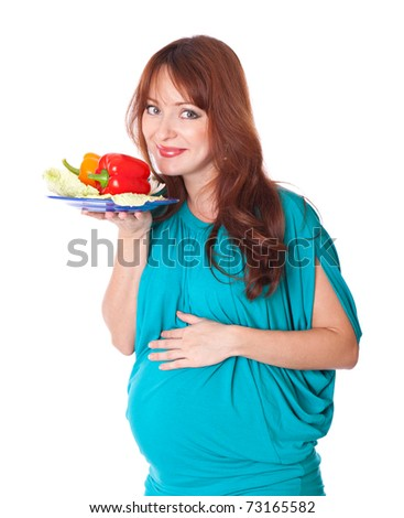 a pregnant woman with a plate of vegetables. isolated on a white background