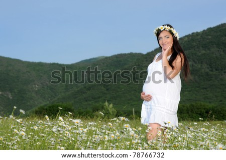 A pregnant young woman in a field of flowers