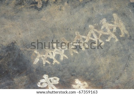 A prehistoric cave painting in Bhimbetka -India , a world heritage site which shows dancing men.