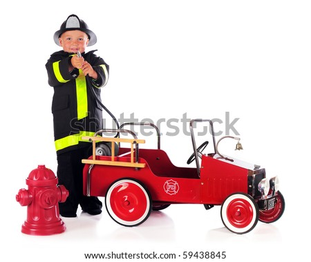 A preschool boy by a fire truck and hydrant and wearing fireman gear, points his hose at the viewer.  Isolated on white.