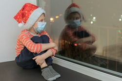a preschool boy in a medical mask and a New Year's cap sits on the windowsill at night and looks out the window. Sad and scary alone in the hospital. Insulation related to covid 19.
