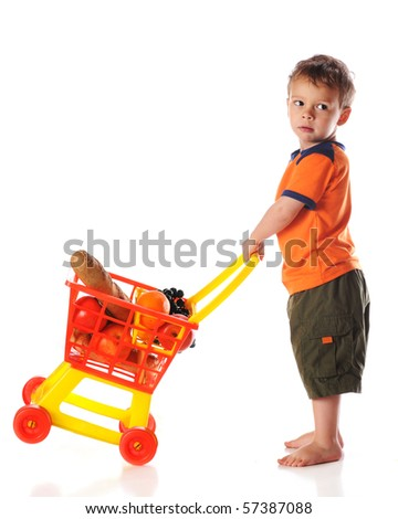 A preschool boy tipping a toy cart full of groceries.  Isolated on white.