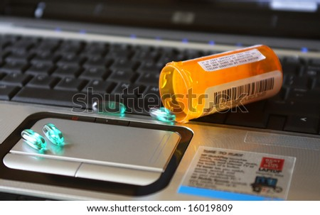A prescription bottle and pills spilled over a keyboard of a laptop computer - stock photo