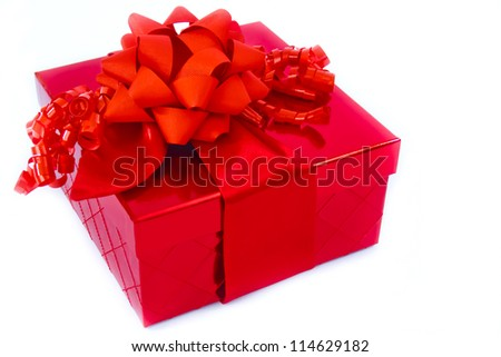 A present in a red gift box is trimmed with a big red bow and red curly ribbons.