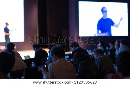 A Presenter with Hand Up Giving Presentation while Audience People Watch in Conference Hall Auditorium. Blurred De-focused Unidentifiable Presenter and Audience. Presentation Screen Video. Technology