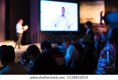 A Presenter with Hands Up Giving Presentation while Audience People Watch in Conference Hall Auditorium. Blurred De-focused Unidentifiable Presenter and Audience. Presentation Screen Video. Education. #1128852014