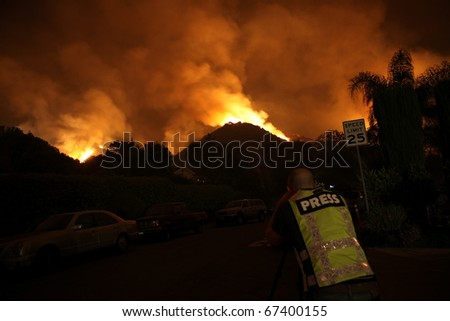A press photographer catches a blazing fire in a residential neighborhood.