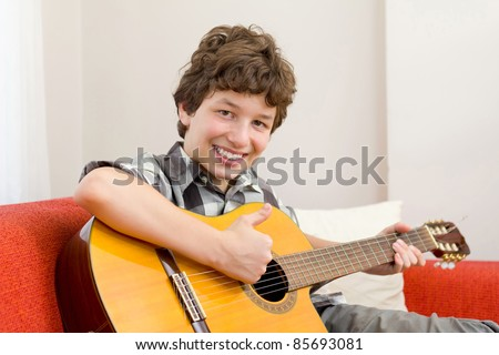 A preteen boy giving a thumbs up and a big happy smile as he holds his guitar and sits on an orange couch.