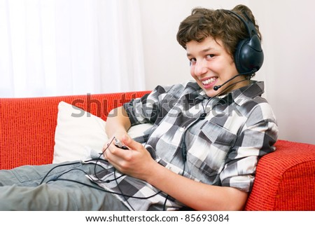 A preteen boy lays back on an orange couch with big headphones as he listens to his mp3 player.