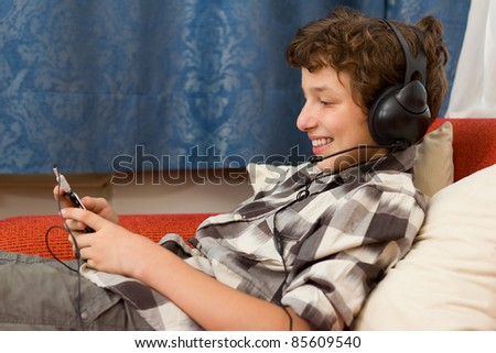 A preteen boy listening to music on his giant headphones as he sits back on an orange couch in a room with blue damask curtains.