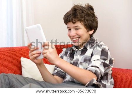 A preteen boy loves reading his electronic book while he sits on an orange sofa.
