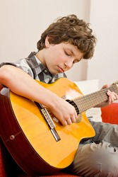 A preteen boy seated on an orange couch with white pillows plays a classic guitar with much feeling.