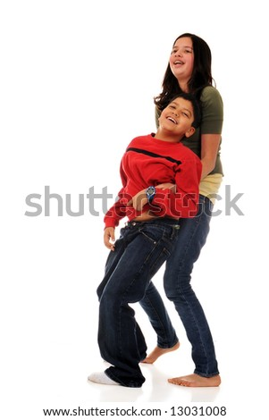 A preteen girl tickling her elementary brother.  Isolated on white.