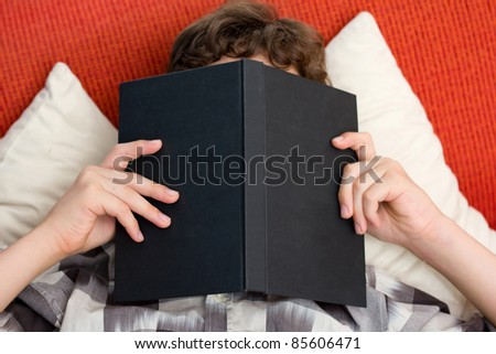 A preten boy reading his book intently as he holds it right up to his face while he lays on an orange couch with yellow pillows.