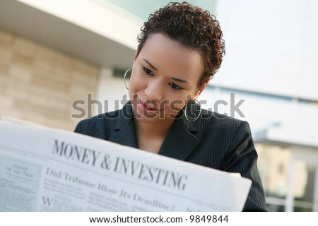 A pretty african american business woman reading the newspaper