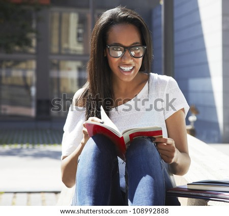 A pretty African American university woman reading at the park