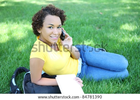 A pretty african american woman talking on the cell phone in park