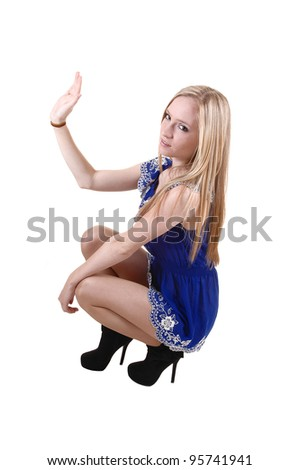 A pretty and slim young woman crouching in her blue short dress and  long blond long hair in black boots for white background in the studio.